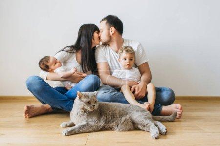 Foto de Padres besándose con dos hijos y el gato gris de pelo corto británico en manos en casa - Imagen libre de derechos