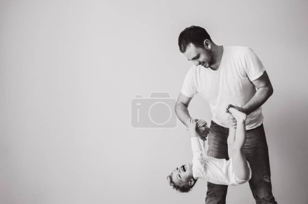 black and white photo of father playing together with little son at home