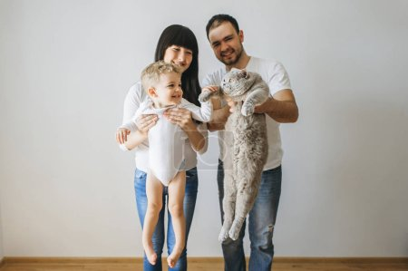 portrait of happy parents holding little toddler boy and grey cat at home
