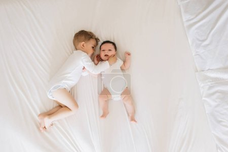 Photo for Overhead view of cute little brothers in white bodysuits lying on bed together at home - Royalty Free Image