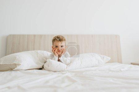 Photo pour Garçon adorable bambin en Body blanc couché sur le lit à la maison - image libre de droit