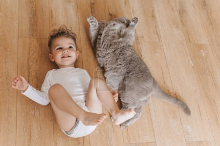 Photo for Overhead view of adorable toddler boy and grey british shorthair cat lying on floor together at home - Royalty Free Image
