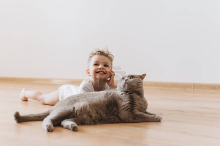 smiling toddler boy and grey british shorthair cat lying on floor together at home