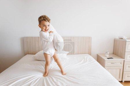 Foto de Niño niño adorable mono blanco jugando con la almohada en la cama en casa - Imagen libre de derechos