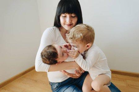 Foto de Madre sentada con dos hijos pequeños en las manos en casa - Imagen libre de derechos