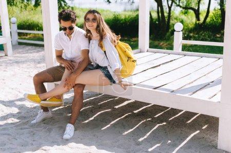 Photo pour Jeune couple assis sur un banc en bois à la plage de sable de la ville - image libre de droit