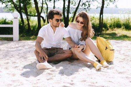 happy couple spending weekend on sandy city beach
