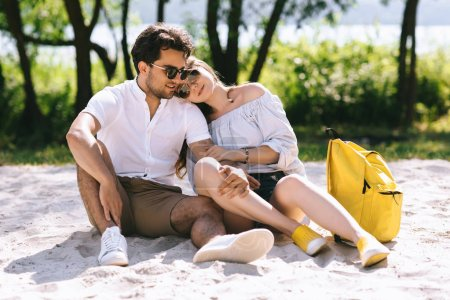 affectionate couple hugging and sitting on sandy city beach