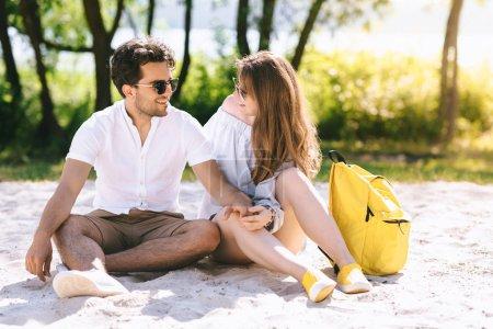 Foto de Feliz pareja sentada en la playa de arena de la ciudad y las manos - Imagen libre de derechos
