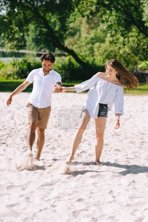 Photo pour Couple main dans la main et en jouant avec le sable sur la plage municipale - image libre de droit
