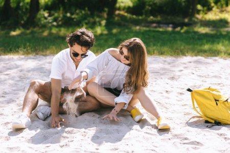 Photo pour Couple en jouant avec le sable sur la plage de la ville de lunettes de soleil - image libre de droit