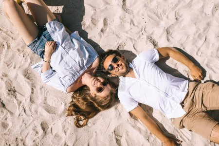 elevated view of smiling couple lying on sandy city beach