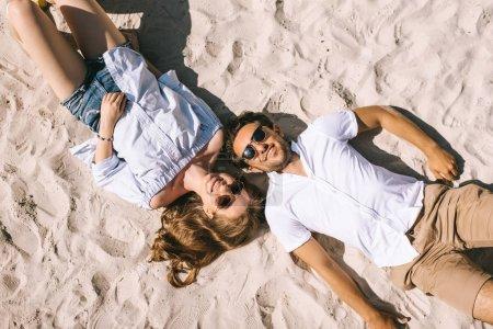 vue du sourire couple allongé sur la plage municipale de sandy