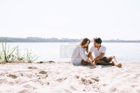 Photo for Affectionate couple sitting on sandy city beach near river - Royalty Free Image