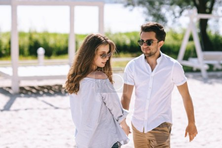 couple in sunglasses and casual clothes at sandy city beach
