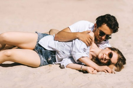 affectionate couple lying and hugging on sandy city beach