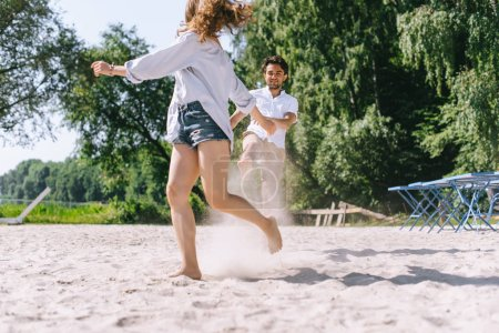 Photo for Smiling couple having fun and running on sandy city beach - Royalty Free Image