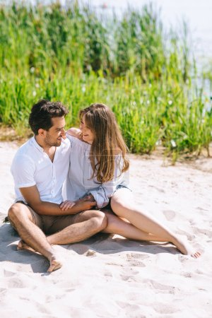 Photo for Happy couple sitting on sandy city beach and looking at each other - Royalty Free Image