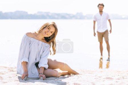 Photo pour Petite amie, assis sur la plage de sandy ville près de la rivière et regardant la caméra - image libre de droit