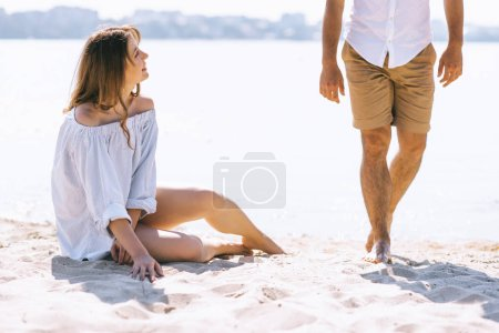Photo pour Cropped image de petite amie, assis sur la plage de sandy city près de rivière et regardant copain - image libre de droit