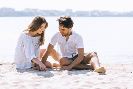 Photo pour Couple de jouer avec du sable sur la plage de la ville près de la rivière - image libre de droit