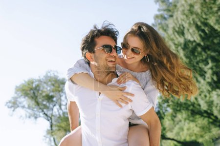 Photo for Low angle view of smiling boyfriend giving piggyback to girlfriend outdoors - Royalty Free Image