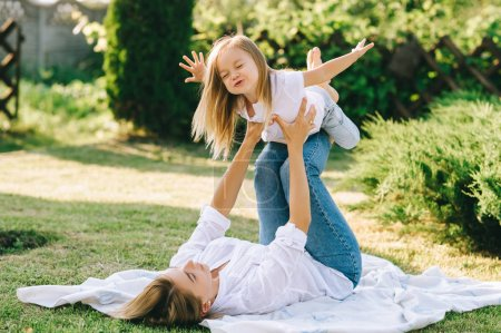 Photo for Mother and happy little daughter having fun together on backyard - Royalty Free Image