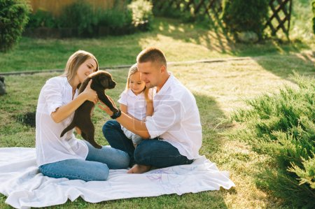 Photo for Parents with little daughter and labrador puppy resting together on backyard - Royalty Free Image
