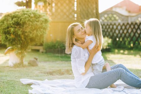 happy mother and little daughter hugging each other while resting on cloth together on backyard