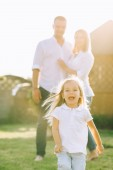 selective focus of little kid running while parents standing behind on backyard