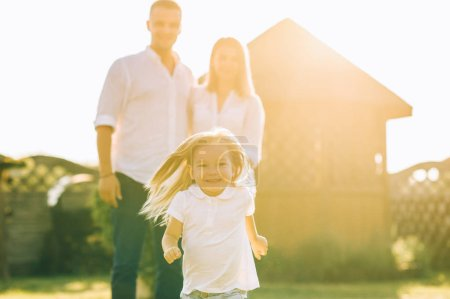 Photo for Selective focus of little kid running while parents standing behind on backyard - Royalty Free Image