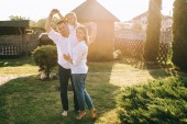 father and daughter piggybacking while mother standing near by on backyard