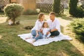 parents and little daughter resting on cloth on ground together on backyard