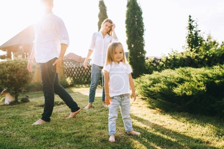 selective focus of little kid with parents behind on backyard