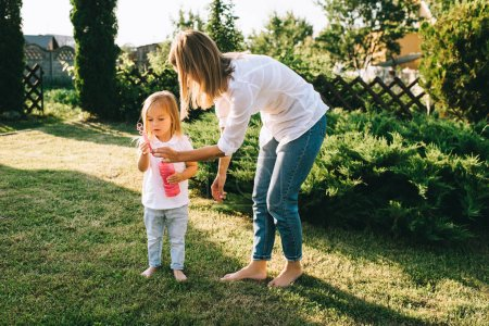 mother helping little daughter blowing soap bubbles on backyard