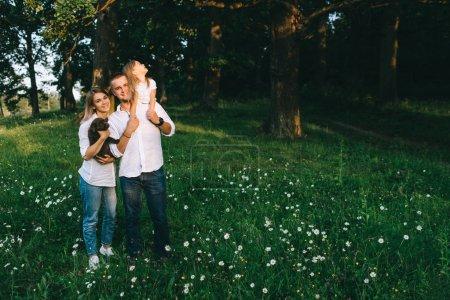 Photo pour Sourire des parents avec la fille et le petit chiot labrador en forêt - image libre de droit