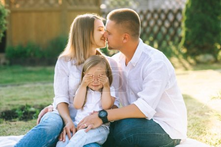 Photo for Parents kissing while little daughter covering eyes while resting together on backyard - Royalty Free Image