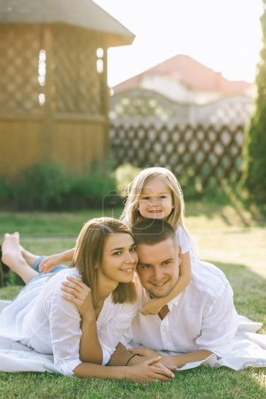 family with little daughter resting on cloth on ground together on backyard