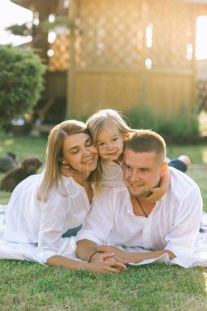 Portrait de sourire famille avec petite fille reposant sur tissu motif ensemble sur l'arrière-cour