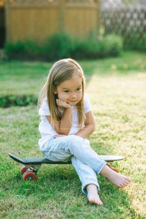adorable little child sitting on skateboard on yard