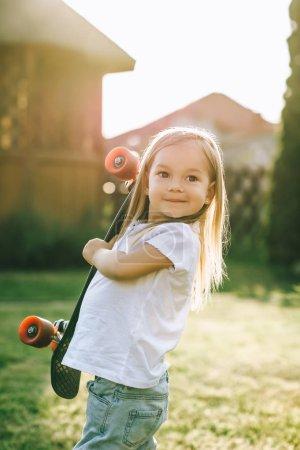 Foto de Retrato de la sonrisa adorable pequeño patinador con tablero de penny en manos en yarda - Imagen libre de derechos