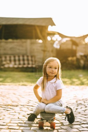 Photo for Adorable little child resting on skateboard on yard - Royalty Free Image