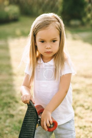 portrait of adorable little child with skateboard in hands on yard