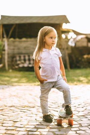 Foto de Vista lateral de niño adorable con patín en yarda - Imagen libre de derechos