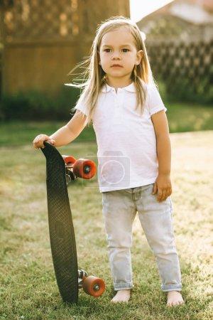 Foto de Adorable pequeño patinador con pie de Junta de penny en yarda - Imagen libre de derechos