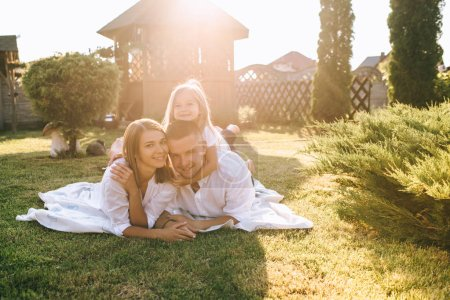 smiling parents and little daughter resting on cloth on ground together on backyard