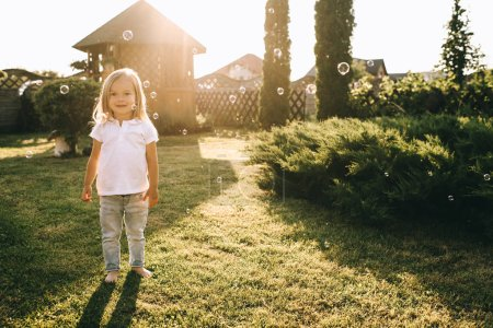 Photo for Cute little blond child looking at camera while standing on backyard - Royalty Free Image