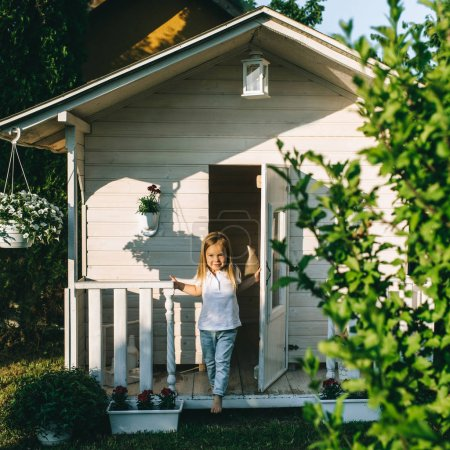 Little kid standing on porch of country house alone on summer day