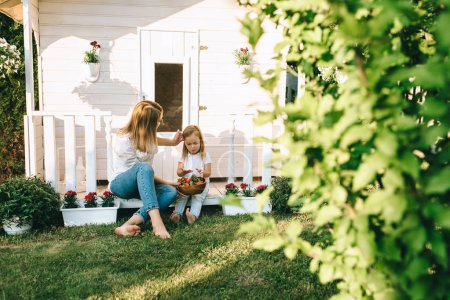 Mother and adorable little kid with bowl of strawberries resting on porch of little country house together