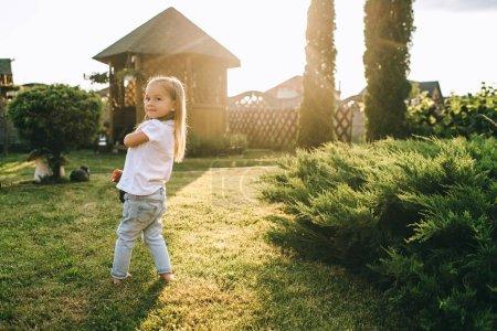Foto de Vista lateral de niño adorable con patín en manos en yarda - Imagen libre de derechos